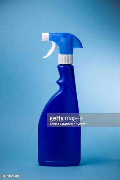 Close-Up Of Spray Bottle Against Blue Background