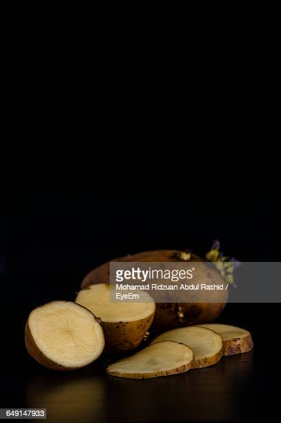 Close-Up Of Sprouting Potatoes With Slices Against Black Background
