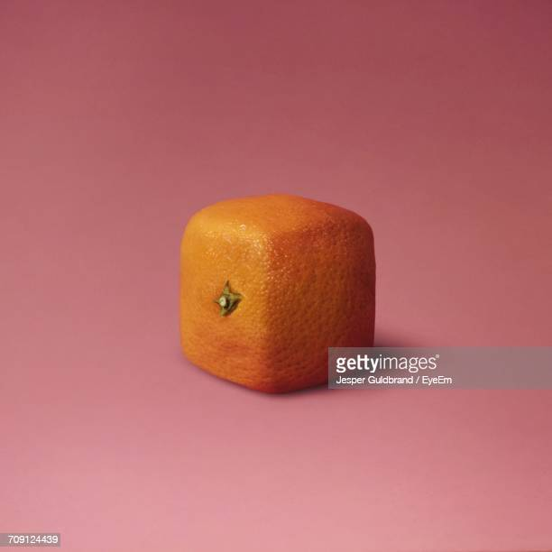 close-up of square orange against pink background - cuadrado composición fotografías e imágenes de stock