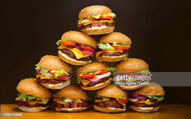 close-up of stack against black background - burger stock pictures, royalty-free photos & images