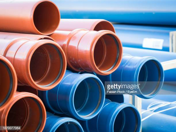 close-up of stack of blue and brown plastic pipes - pipe tube stock pictures, royalty-free photos & images