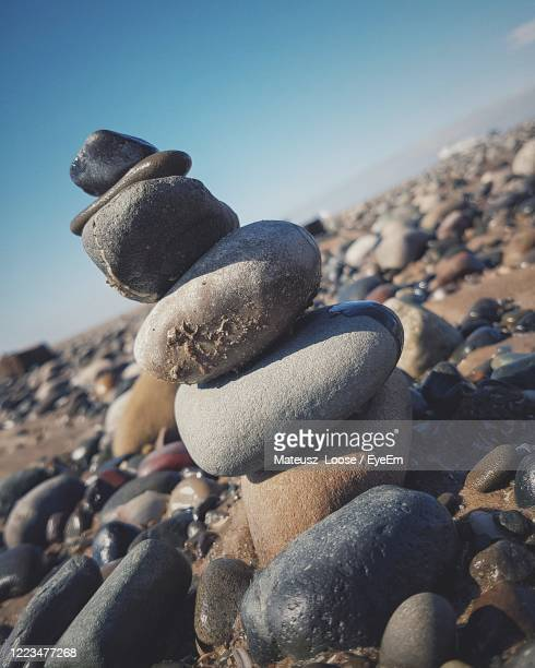 close-up of stack of pebbles on sand at beach - blackpool beach stock pictures, royalty-free photos & images