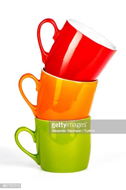 close-up of stacked colorful coffee cups on white background - mug stock pictures, royalty-free photos & images