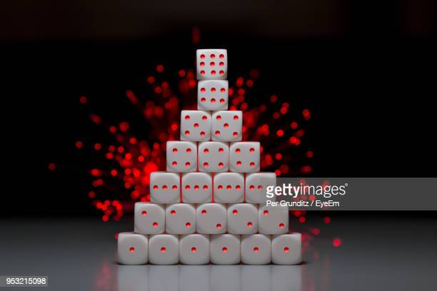 Close-Up Of Stacked Dices On Table Against Black Background