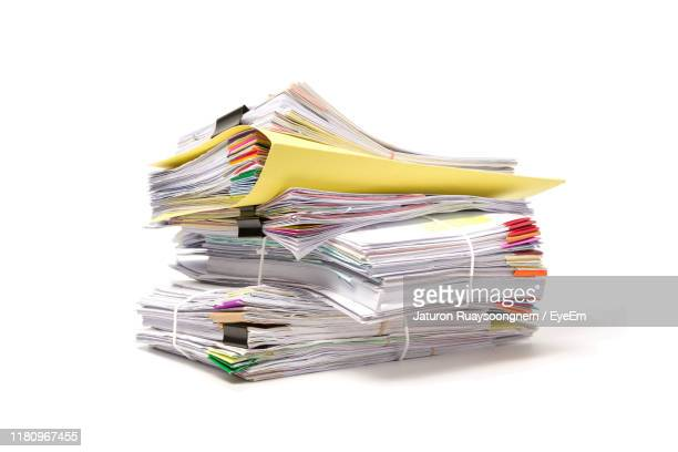 close-up of stacked files and papers against white background - papierkram stock-fotos und bilder