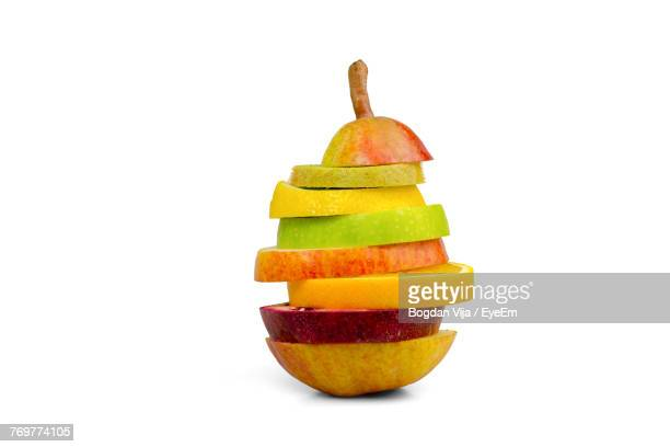 Close-Up Of Stacked Fruit Slices Against White Background