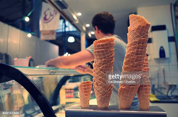 Close-Up Of Stacked Ice Cream Cones By Man In Parlor