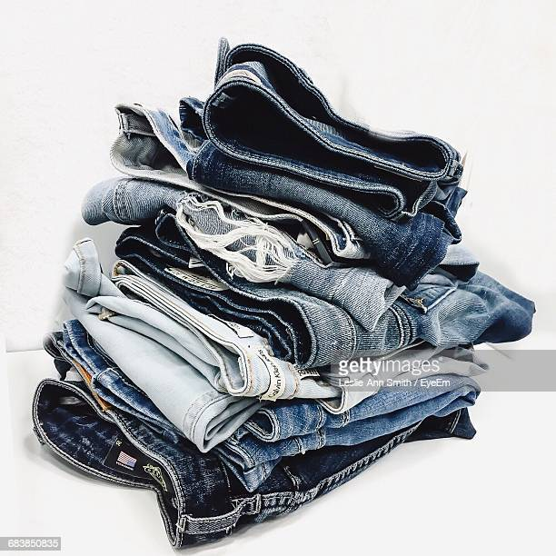 Close-Up Of Stacked Jeans Against White Background