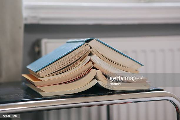 Close-up of stacked open books on table
