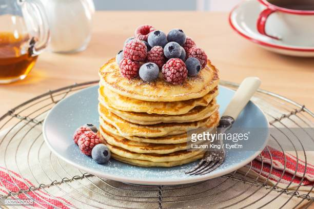 close-up of stacked pancakes with berries on table - pancake stock pictures, royalty-free photos & images