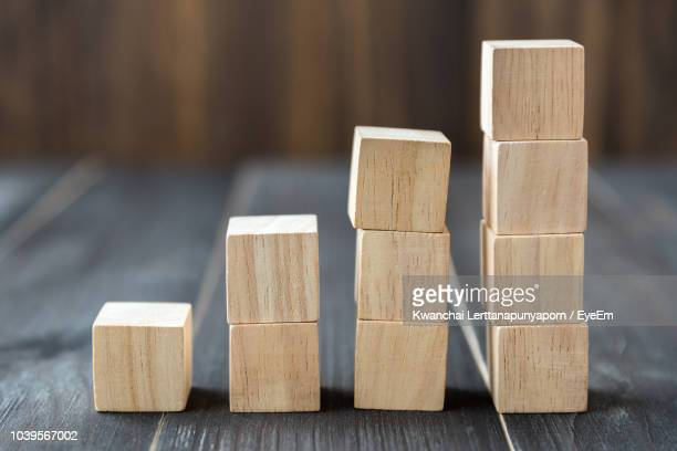 close-up of stacked wooden blocks on table - toy block stock pictures, royalty-free photos & images