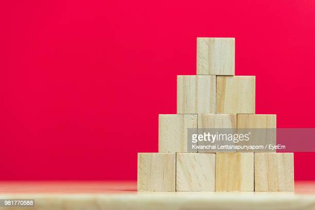 Close-Up Of Stacked Wooden Toy Blocks On Table Against Red Background