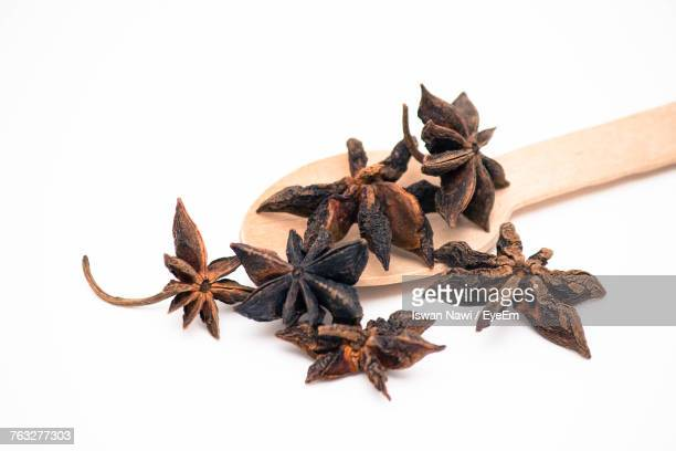 Close-Up Of Star Anises With Spoon Against White Background