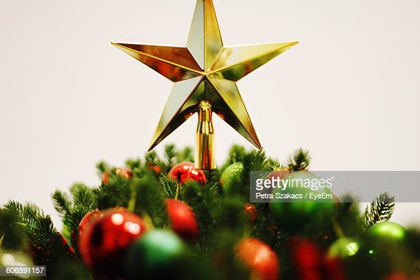 Close-Up Of Star Shape On Christmas Tree Over White Background