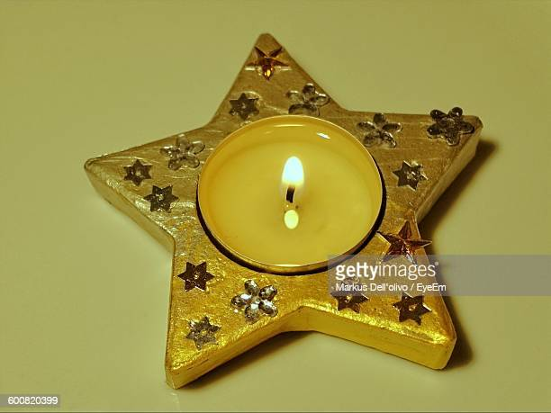 Close-Up Of Star Shape Tea Light Candle On Colored Background