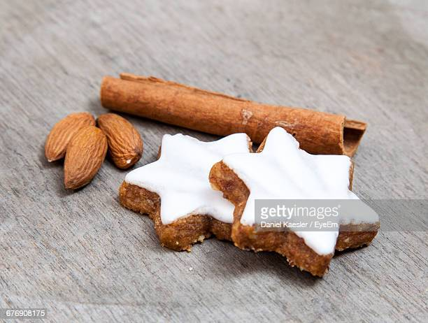 Close-Up Of Star-Shaped Cinnamon Cookies And Almonds On Wooden Table