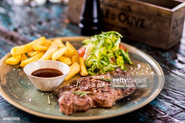 Close-Up Of Steak And Fries Served On Plate