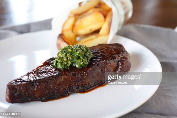 close-up of steak with french fries served in plate on table - fries stock-fotos und bilder