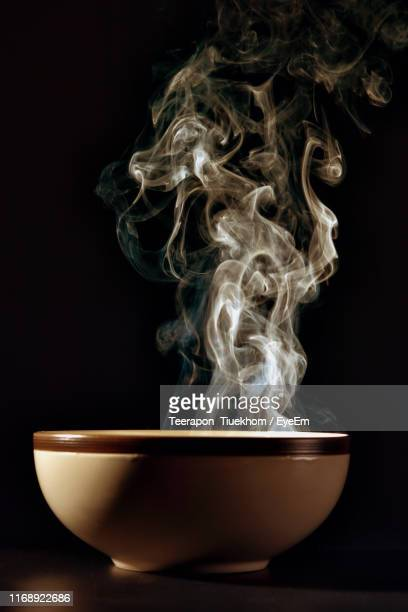 close-up of steam coming out from hot bowl against black background - steam stock pictures, royalty-free photos & images