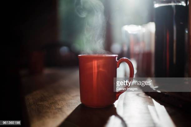close-up of steam emitting from coffee cup on table at home - dampf stock-fotos und bilder