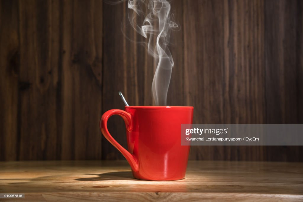Close-Up Of Steam Emitting From Coffee Cup On Table : Stock Photo