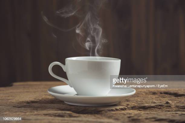 close-up of steam emitting from coffee cup on wooden table - platillo fotografías e imágenes de stock