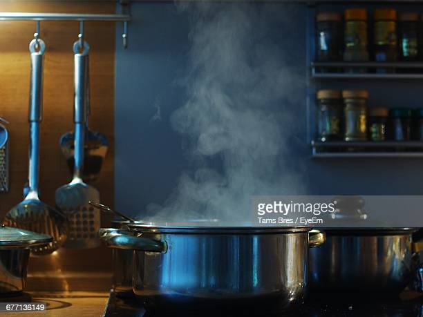 close-up of steaming pot on stove in kitchen - cooking utensil stock photos and pictures