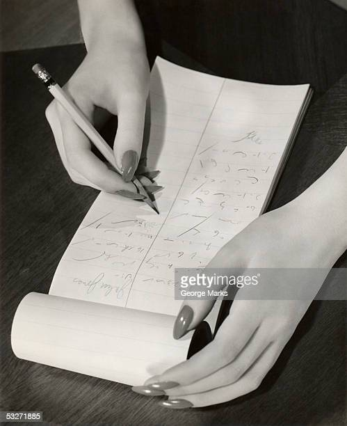 Close-up of stenographer's hands taking notes