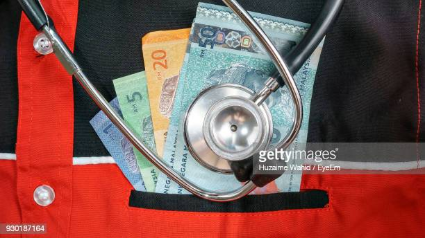 Close-Up Of Stethoscope And Money On Shirt