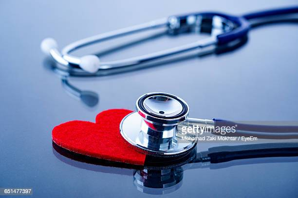 Close-Up Of Stethoscope And Red Heart Shape On Table