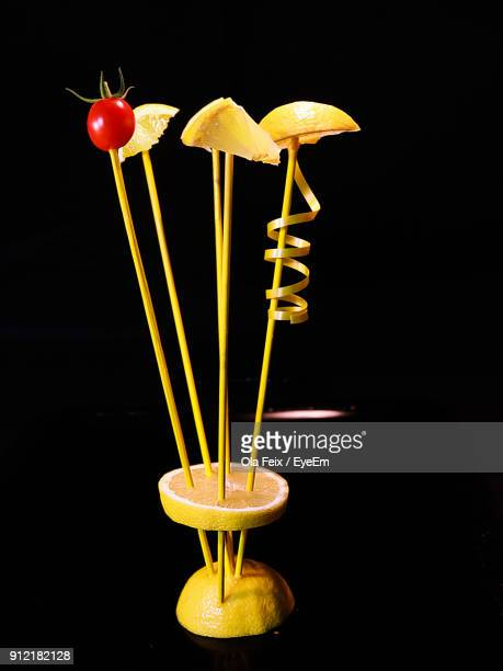 Close-Up Of Sticks With Lemon Slices And Tomatoes Against Black Background