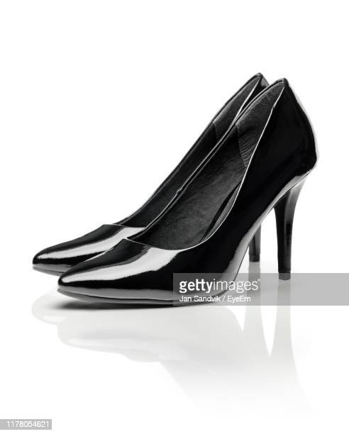close-up of stiletto over white background - black shoe stock pictures, royalty-free photos & images