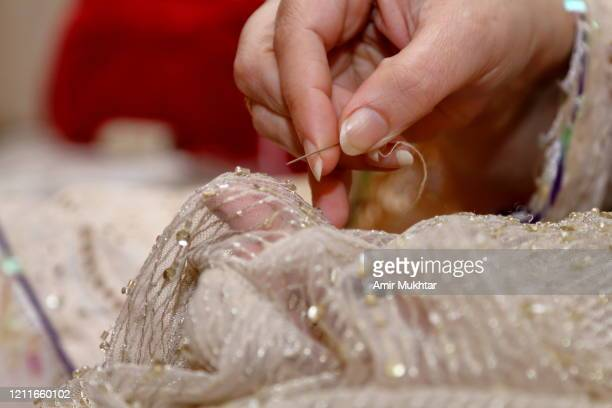 closeup of stitching embroidered clothes with a needle and thread. - fashion collection stock pictures, royalty-free photos & images