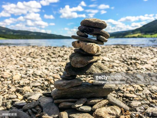 Close-up of stone cairn on a pebble beach with mountains and lake in the background