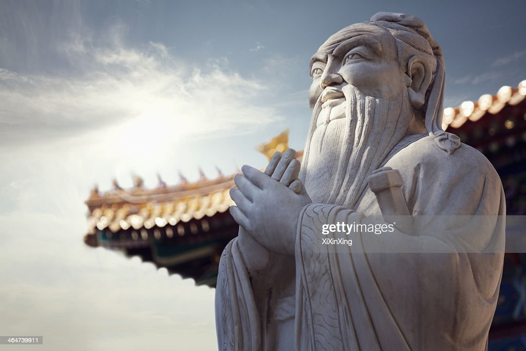 Close-up of stone statue of Confucius, pagoda roof in the background : Stock Photo