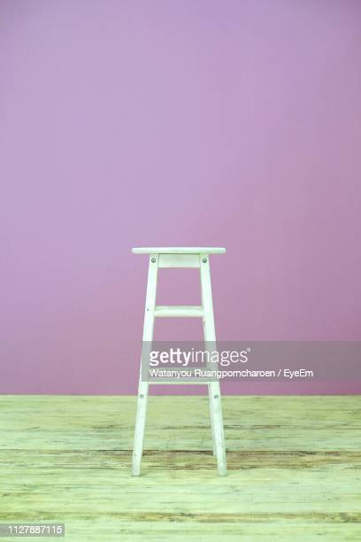 close-up of stool on hardwood floor against purple wall - stool stock pictures, royalty-free photos & images