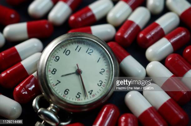 close-up of stopwatch with capsules - dosis stock-fotos und bilder