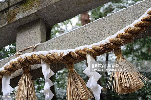 Close-Up Of Straw Festoon Hanging On Stone Gate