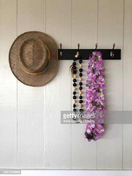close-up of straw hat with bead necklace and garland hanging on hooks at home - purple hat stock pictures, royalty-free photos & images