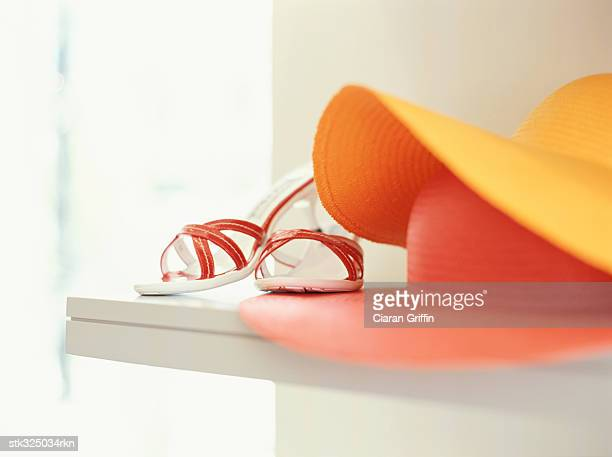close-up of straw hats with a pair of sandals in a store - orange shoe stock photos and pictures