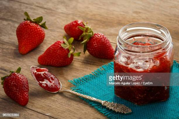 close-up of strawberries by preserves in jar on table - jam stock pictures, royalty-free photos & images
