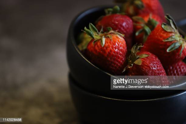 closeup of strawberries on dark background - nanette j stevenson stock photos and pictures