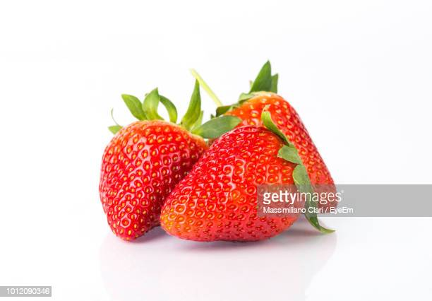 close-up of strawberries over white background - strawberry stock pictures, royalty-free photos & images