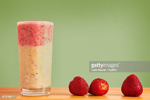 Close-Up Of Strawberry And Banana Smoothie On Wooden Table Against Green Background