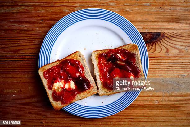 Close-Up Of Strawberry Jam With Bread In Plate On Table
