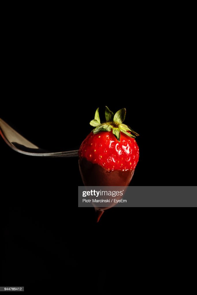 Close-Up Of Strawberry On Fork Over Black Background : Stock Photo