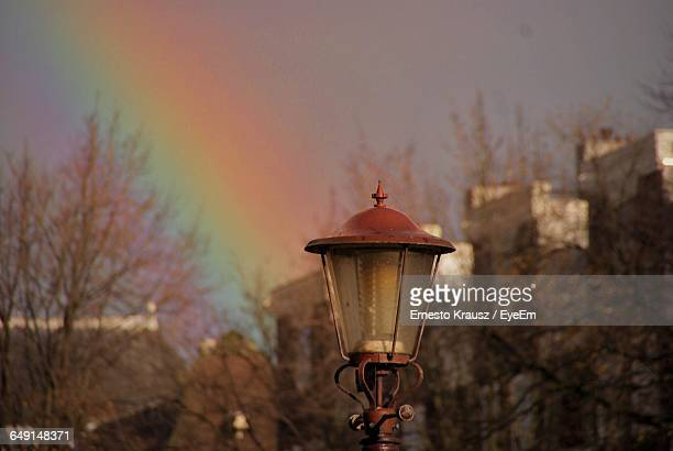 close-up of street light against rainbow at dusk - krausz stock-fotos und bilder