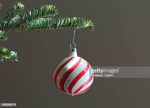 Close-Up Of Striped Bauble Hanging From Christmas Tree Against Wall