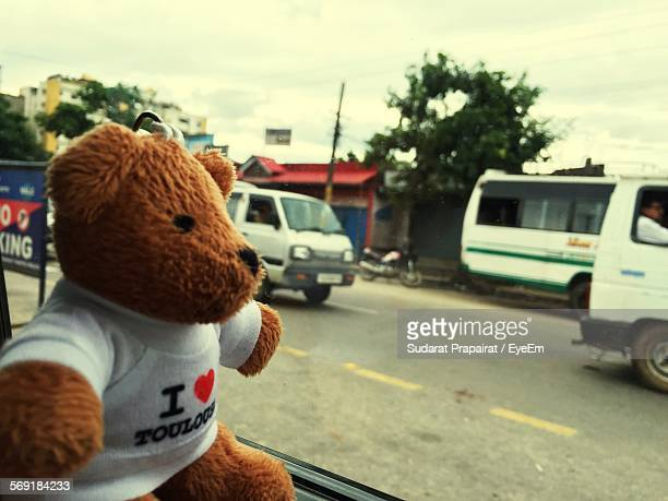 Close-up of stuffed teddy bear by glass window in vehicle on street