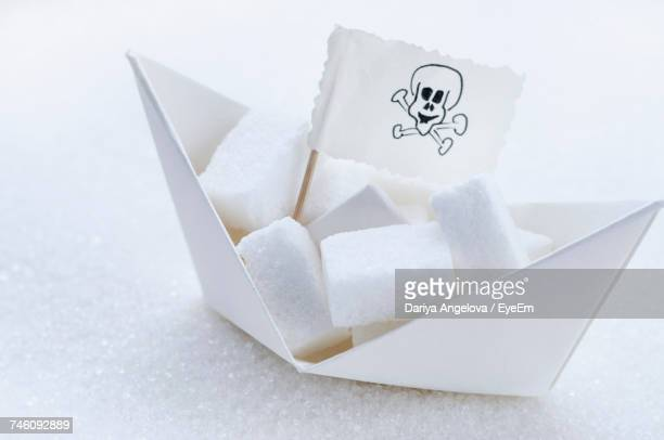 Close-Up Of Sugar Cubes And Danger Sign In Paper Boat